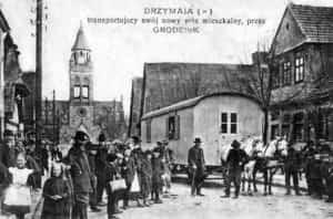 Ilustracja przedstawia Michała Drzymałę ze swoim wozem w Grodzisku Mazowieckim.