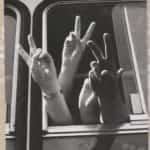 Zdjęcie ludzi w autobusie pokazujących przez szybę znak Solidarności.